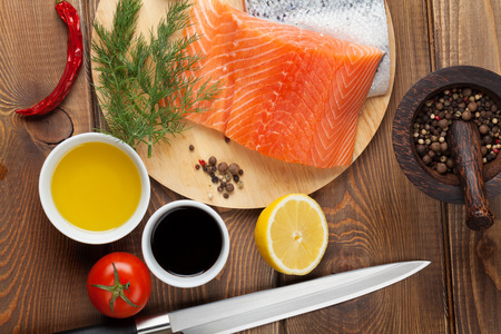 cutting board: Salmon, spices and condiments on wooden table. Top view Stock Photo