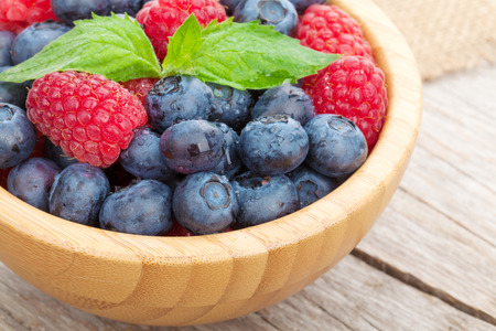 raspberry: Blueberries and raspberries bowl on wooden table