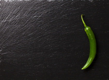 black stone: Green chili pepper on black stone table with copy space