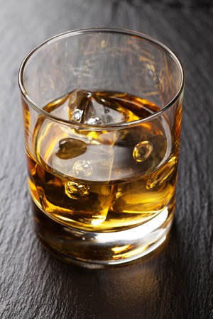 Glass of whiskey with ice on black stone table photo
