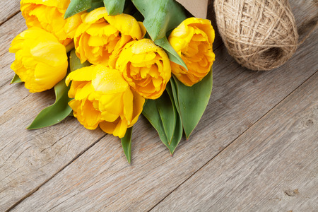Yellow tulips over wooden table background photo