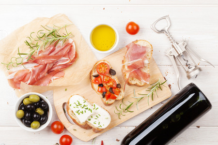 white cheese: Bruschetta with cheese, tomatoes and prosciutto on cutting board