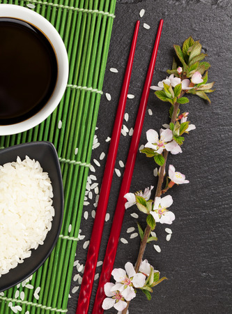sauce bowl: Japanese sushi chopsticks, soy sauce bowl, rice and sakura blossom on black stone background