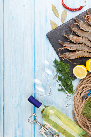 food and wine: Fresh raw tiger prawns, spices and white wine on wooden table with copy space Stock Photo