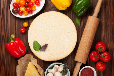 pizza dough: Pizza cooking ingredients. Dough, vegetables and spices. Top view with copy space Stock Photo