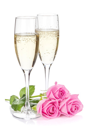 Two champagne glasses and pink rose flowers. Isolated on white background photo
