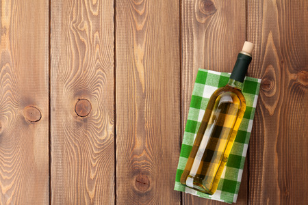 vino: White wine bottle over towel on wooden table background. Top view with copy space Stock Photo