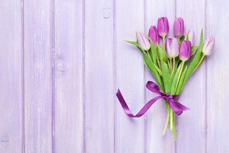 Paarse tulpen over houten tafel. Bovenaanzicht met een kopie ruimte