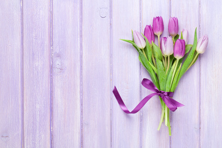 violet flowers: Purple tulips over wooden table. Top view with copy space