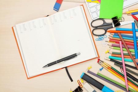 School en kantoorbenodigdheden over bureaulijst. Bovenaanzicht met Kladblok voor kopie ruimte