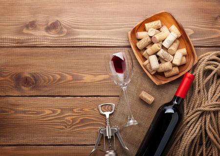 Rode wijn fles, glas wijn, kom met kurken en kurkentrekker. Uitzicht van boven op rustieke houten tafel achtergrond