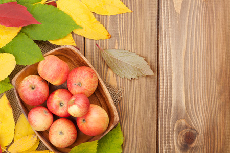 woden: Apples in bowl and colorful autumn leaves on woden background with copy space Stock Photo