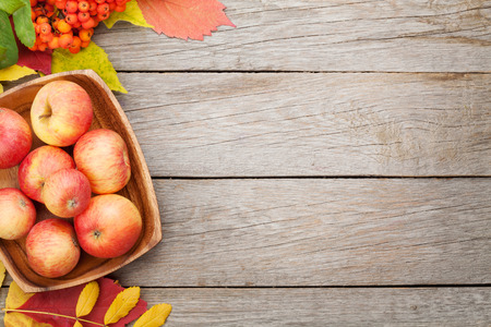 Apples in bowl and colorful autumn leaves on woden background with copy space Stock Photo