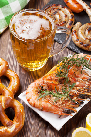 Beer mug, grilled shrimps, sausages and pretzel on wooden table Stock Photo