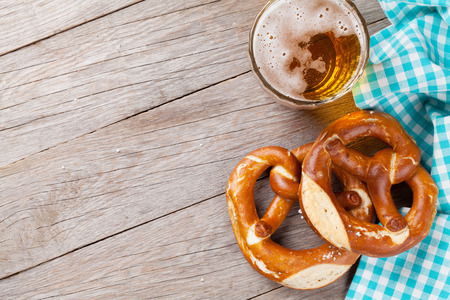 Beer mug and pretzel on wooden table. Top view with copy space 写真素材