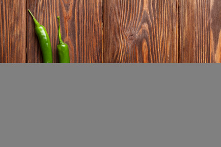 chili peppers: Green chili peppers on wooden table with copy space Stock Photo