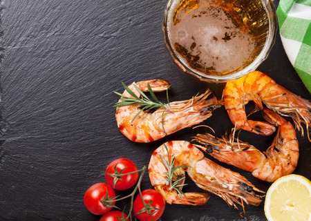 bbq grill: Beer mug and grilled shrimps on stone plate. Top view with copy space Stock Photo