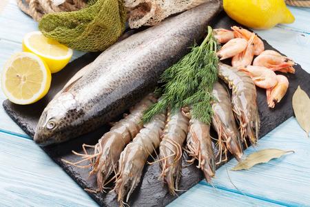 gamba: Los alimentos frescos del mar cruda con especias en la placa de piedra más de fondo de la tabla de madera. Vista superior Foto de archivo