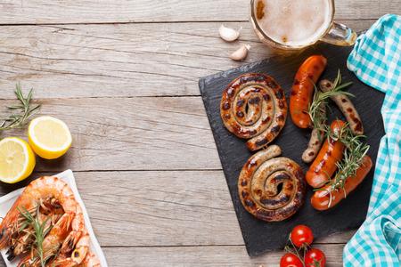 gamba: Taza de cerveza, a la plancha camarones y embutidos en la mesa de madera. Vista superior con espacio de copia