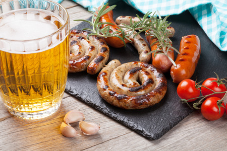 grill: Beer mug and grilled sausages on wooden table Stock Photo
