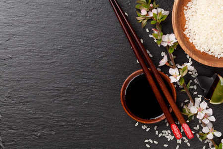 Palillos de sushi japonés, cuenco de salsa de soja, arroz y flor de sakura en negro el fondo de piedra. Vista superior con espacio de copia Foto de archivo - 41540363