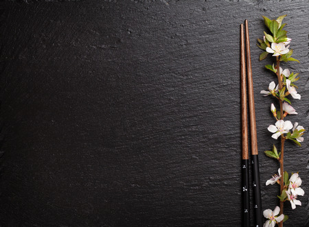 Japanese sushi chopsticks and sakura blossom on black stone background. Top view with copy space