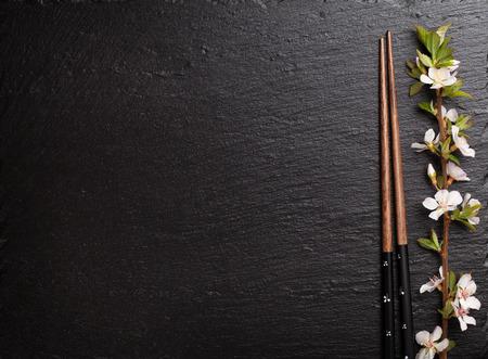 flor de sakura: Palillos de sushi japonés y flor de sakura en negro el fondo de piedra. Vista superior con espacio de copia Foto de archivo