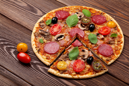 food on table: Italian pizza with pepperoni, tomatoes, olives and basil on wooden table Stock Photo