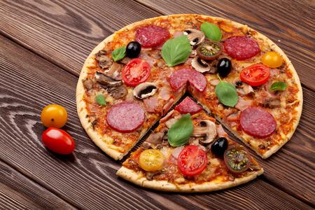 comida italiana: Pizza italiana con pepperoni, tomate, aceitunas y albahaca sobre la mesa de madera