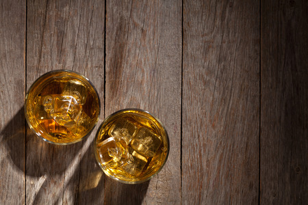 liquor glass: Glasses of whiskey with ice on wooden table. Top view with copy space