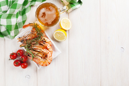 prepared shrimp: Beer mug and grilled shrimps on wooden table. Top view with copy space Stock Photo