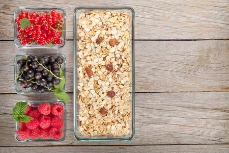 Healthy breakfast with muesli and berries. View from above on wooden table with copy space Banco de Imagens