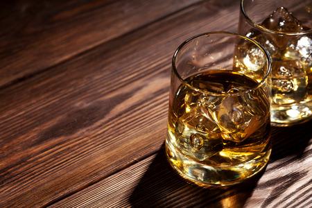 コピー スペースの木製のテーブルの上の氷とウイスキーのグラス