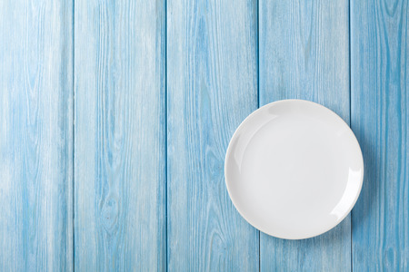 Empty plate on blue wooden background. Top view with copy space Banco de Imagens