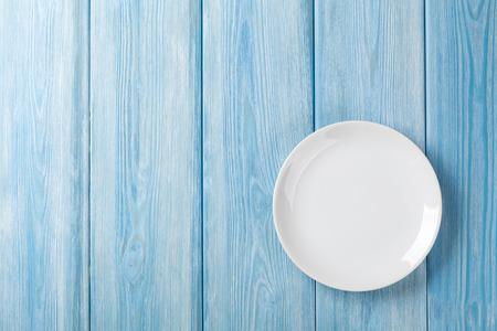 tabulka: Prázdný talíř na modrém dřevěném pozadí. Pohled shora s kopií vesmíru