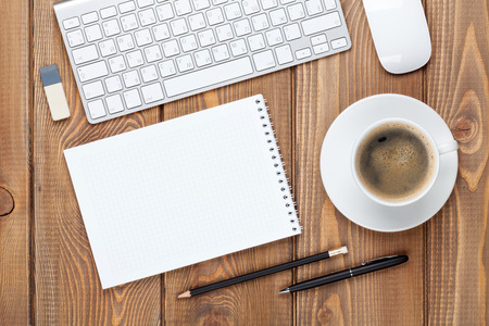 office space: Office desk table with computer, supplies and coffee cup. Top view with copy space Stock Photo