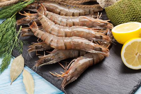 prawn: Fresh raw tiger prawns and fishing equipment on wooden table
