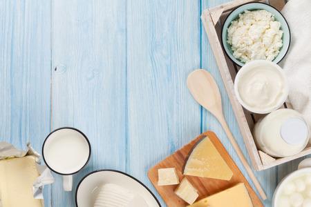 木製テーブルの上の乳製品。サワー クリーム、牛乳、チーズ、卵、ヨーグルト、バター。コピー スペース平面図