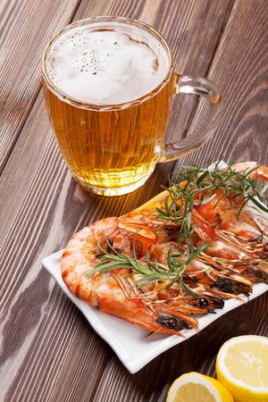 camaron: Taza de cerveza y camarones a la parrilla en la mesa de madera