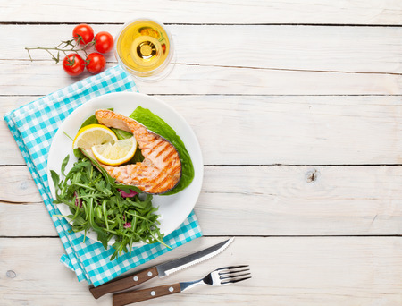 vegetable background: Grilled salmon and white wine on wooden table. Top view with copy space Stock Photo