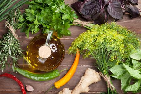 aceite oliva: Hierbas frescas del jard�n y el aceite de oliva en la mesa de madera. Vista superior