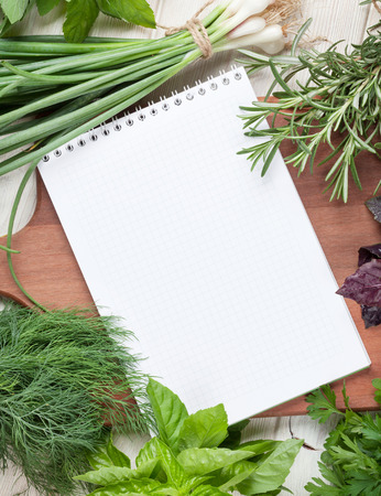 cutting: Fresh garden herbs and notepad for recipes on wooden table