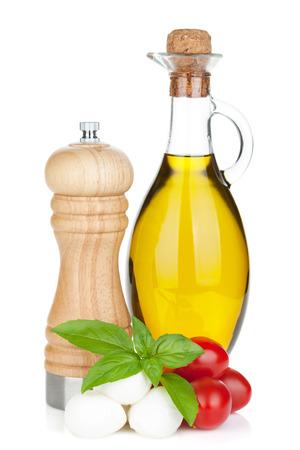oil of olive: queso mozzarella con tomates cherry, albahaca y aceite de oliva con pimienta agitador. Aislado en el fondo blanco