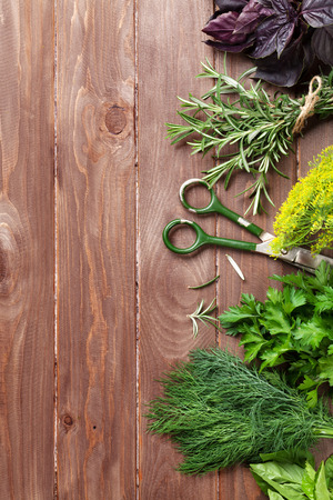 kulinarne: Fresh garden herbs over wooden table. Top view with copy space