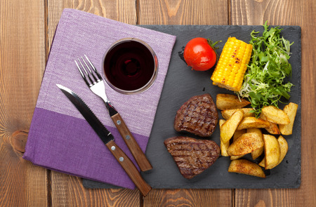grilled potato: Steak with grilled potato, corn, salad and red wine on wooden table. Top view Stock Photo
