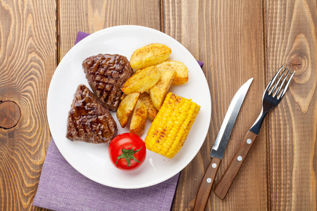 Steak with grilled potato, corn and tomato over wooden table. Top view with copy space