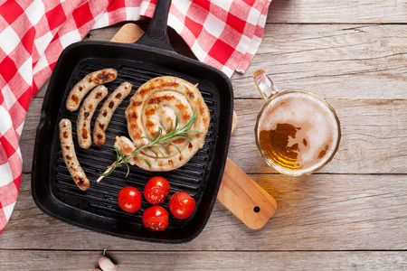 meat grill: Grilled sausages and beer mug on wooden table. Top view Stock Photo
