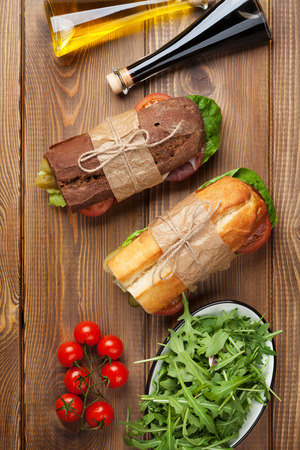 サラダ、ハム、チーズ、トマト、サラダ、木製のテーブルの上のスパイスと 2 つのサンドイッチ。トップ ビュー