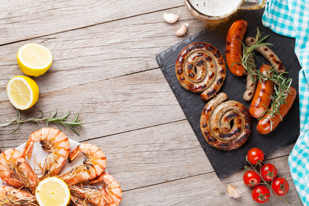 shrimp: Beer mug, grilled shrimps and sausages on wooden table. Top view with copy space