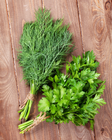 dill: Fresh garden dill and parsley herbs on wooden table. Top view